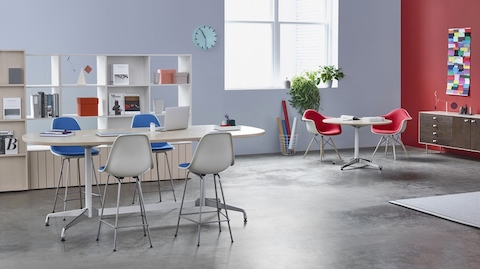 A Workshop setting is built around a group of four Eames Stools around a standing-height Eames Table, with a pair of upholstered Eames Molded Fiberglass armchairs at a small Eames Table below a nearby window.