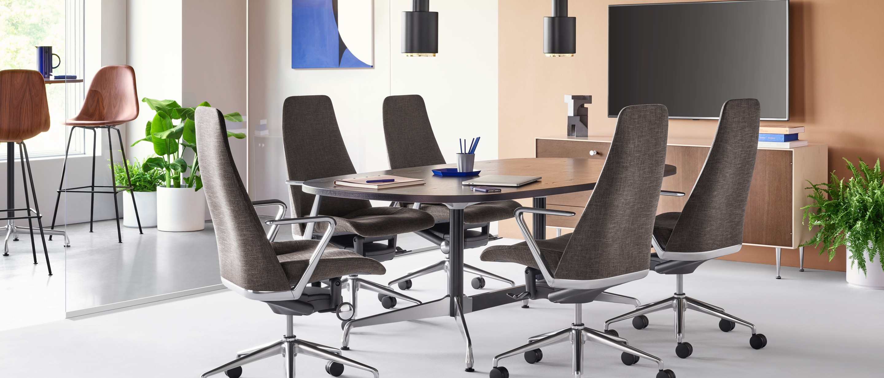 A meeting space setting featuring four black Taper Chairs surrounding an ebony Eames Table. A Nelson Thin Edge Chest sits beneath a TV against the back wall and two Eames Molded Wood Stools cluster around a tall table in the background.