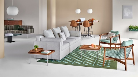 A casual work setting featuring Module Lounge Seating and the Crosshatch Chair. The background features a gathering of Eames Molded Wood Stools and a lounge area.