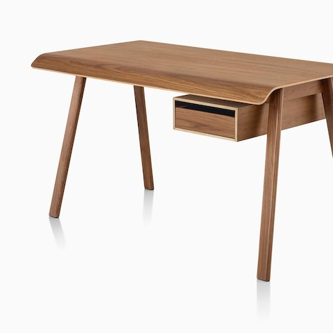 A Distil Desk in a medium wood finish, viewed from an angle. Select to go to the all products page for the Herman Miller Collection.