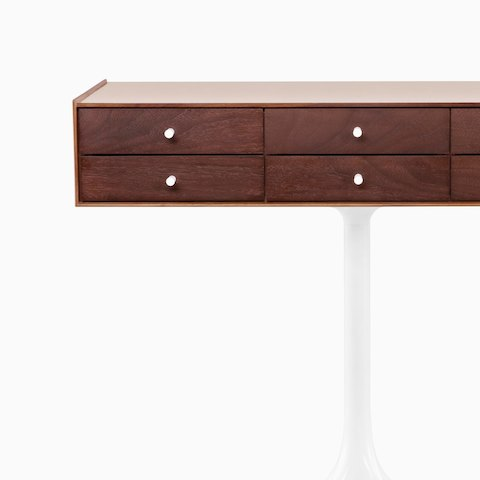 A horizontal six-drawer Nelson Miniature Chest with a medium finish and white pedestal base, viewed from the front. Select to go to the all products page for the Herman Miller Collection.