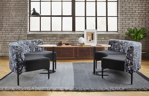 Matching patterned gray Symbol Sofas and wooden side tables face each other atop a two-tone gray rug. Behind them is a wooden credenza and black floor lamp.