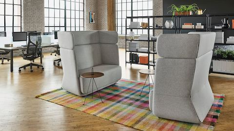 Matching light gray high-back Basket Sofas and wooden side tables sit atop a colorful plaid rug. Separating the space is a black Magis Steelwood Shelving bookcase and workstations with Cosm chairs.