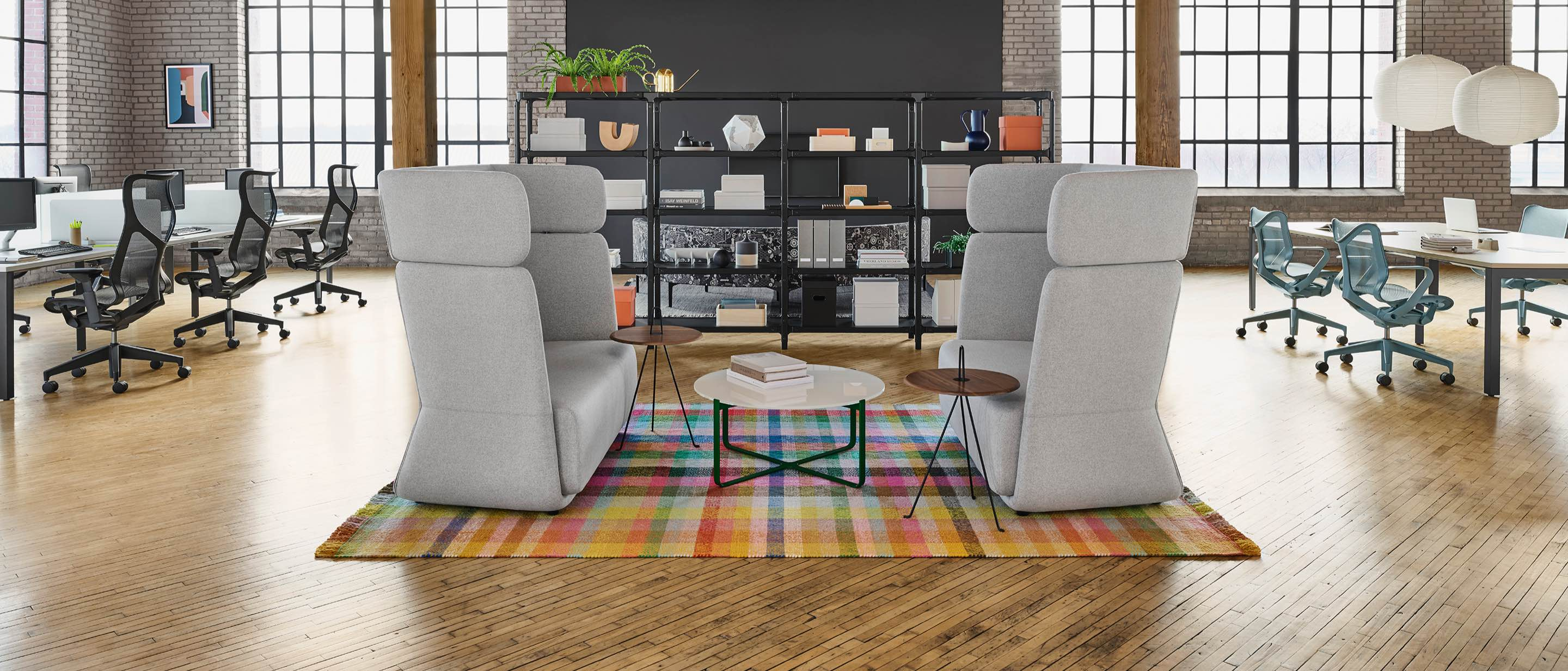 A loft space with exposed wooden beams. Featured are the matching gray high-back sofas, a colorful plaid rug, and black metal open shelving, surrounded on both sides with a cluster of workstations and rolling Cosm chairs.