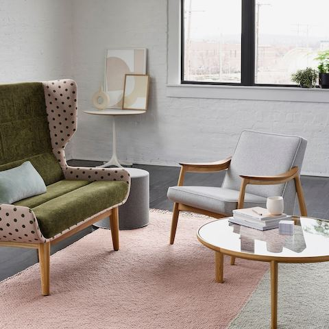 Green and pink polka-dotted high-back Hush Sofa with light gray upholstered Aspen Chair, wood and glass round coffee table.