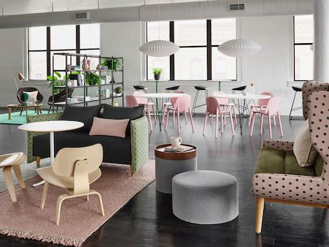 Green and pink rug and polka-dotted sofas, wooden lounge chairs, and gray poufs sit in front of white café tables and pink guest chairs and black metal bookcase, separating a lounge space.