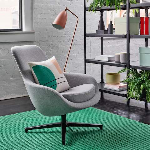 Light gray Saiba Lounge Chair and modern pillow on a bright green rug with pink floor lamp and black metal bookcase filled with ferns, vases, and books.