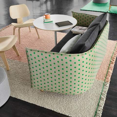 Polka-dotted green and gray Cloud Sofa, Eames Plywood Chairs, and round white table sit atop a pastel green and pink rug.