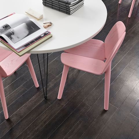 Round white table with black hairpin legs allow books to spread out on top. Pastel pink wooden chairs tuck in underneath.