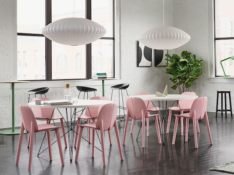 Café white tables and pink chairs sit in front of tall green cocktail tables, sleek black stools, and tall fiddle tree, underneath two white Nelson Bubble Lamps.