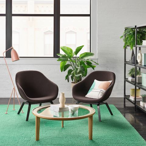 Dark gray lounge chairs, pink floor lamp, tropical plant, and wood and glass coffee table sit atop bright green rug, next to open black metal Magis Steelwood Shelving bookcase.
