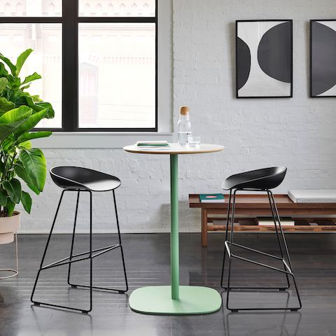 Tall green cocktail table flanked by two black barstools, large tropical plant, and low wooden bench.