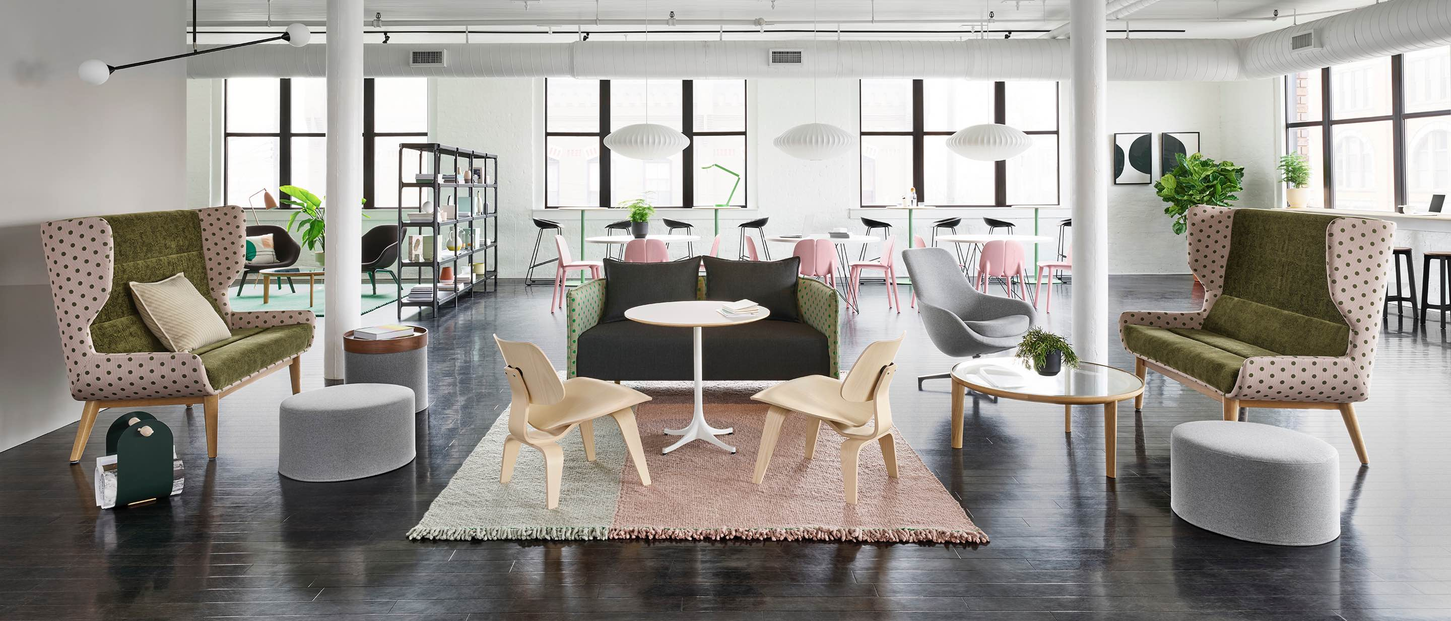Open bright loft space with pink and green polka-dotted sofas, two-tone rug, wooden Eames lounge chairs, and gray poufs in front of trio of café tables and pink chairs.