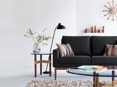 A sofa with dark gray fabric upholstery in a living room behind a glass top coffee table with brass base with a modern wall clock.
