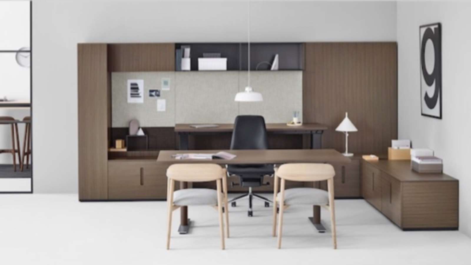 Stark white room featuring dark wood veneer casegoods desk system. A simple matching desk, black leather rolling chair, and light wood low-back guest chairs sit in front.