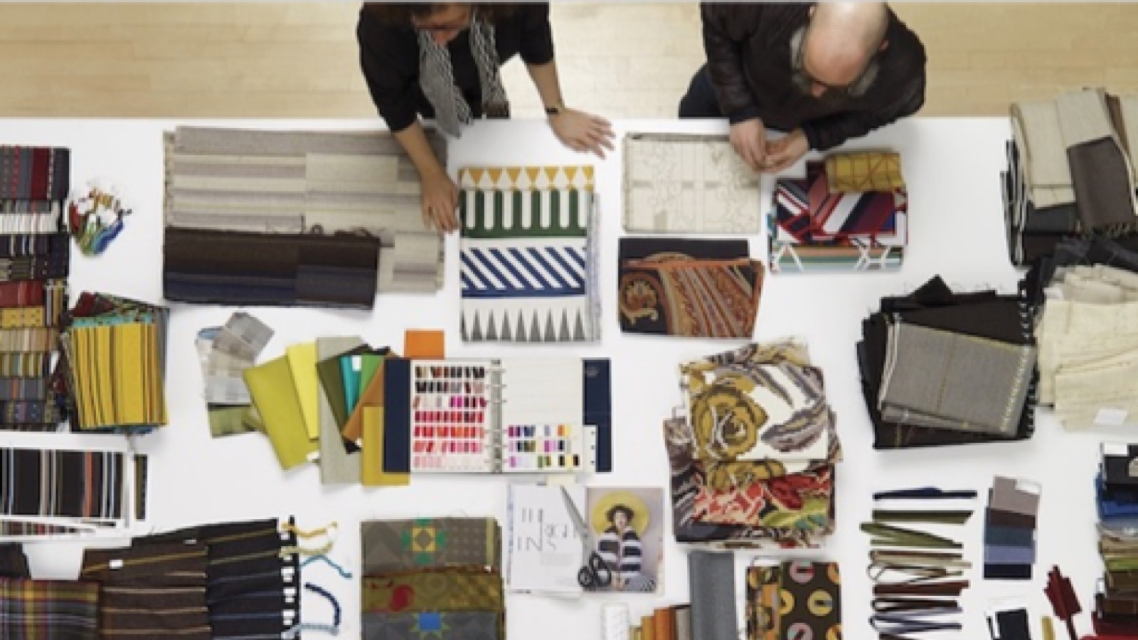 Overhead shot of two people discussing fabric swatches, ribbons, and swatchbook on large white table. Fabrics include a variety of striped and floral patterns, in a rainbow of colors.