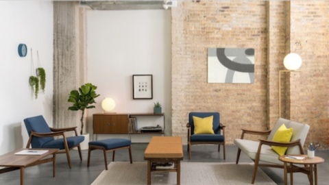 Exposed brick wall surrounded by upholstered navy and light gray upholstered lounge chairs and loveseat, with wooden coffee and side tables and wall console.