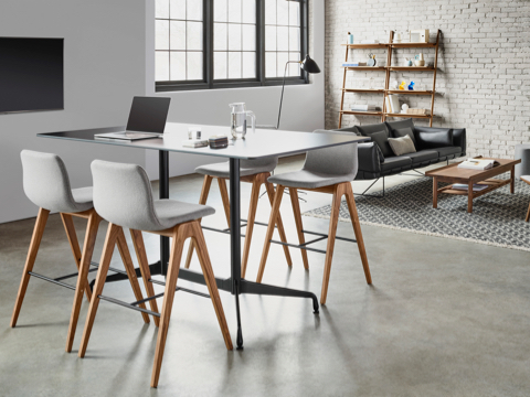Collaborative tall table with gray upholstered barstools. Behind, sits a modern black leather couch with open bookshelf, wooden coffee table, and upholstered wooden lounge chair atop a patterned rug.