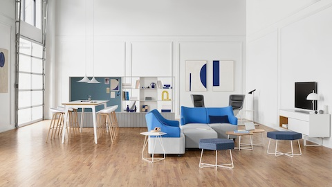 Bright white office space with tall meeting table and wooden stools sitting next to built-in shelving. Flexible blue and gray modular furniture and wire side tables and poufs face a white credenza holding a flat screen TV.