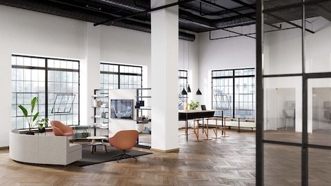 An open floor workplace with soft seating, a communal table and phone booths.