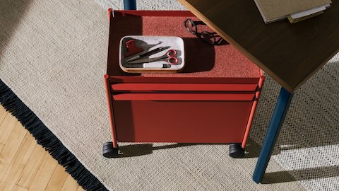 A red OE1 Storage Trolley with casters, nesting under an OE1 Rectangular Table with dark brown surface and blue legs.