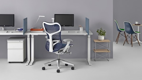 A blue Mirra 2 office chair at a workpoint with a sit-to-stand desk. Select to review Herman Miller's ergonomics research.