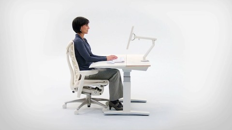 Profile view of a seated woman achieving correct ergonomic posture. Select to view a video about sitting better.