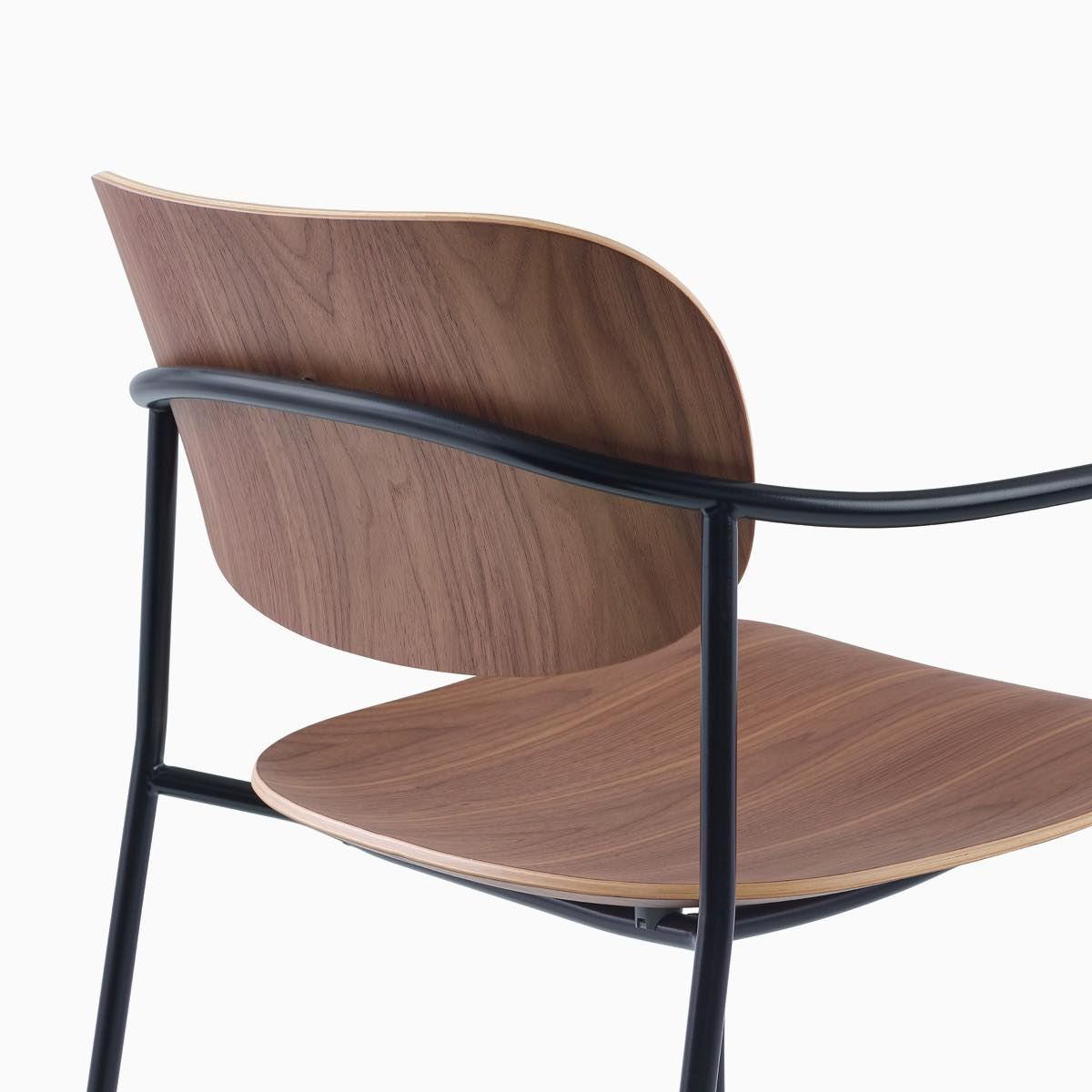 Detail image of Portrait Chair with Walnut seat and back, and black frame with arms.