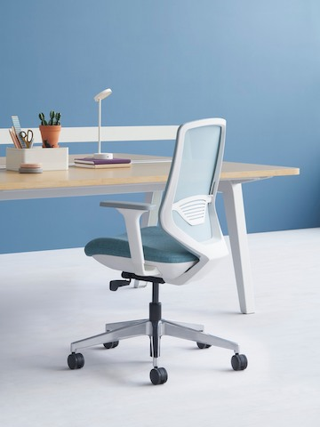 A gray POSH Express 2 Chair with a white frame and blue textile seat next to an Optimis Desk in a workstation setting.