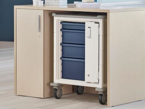 A soft white Procedure and Supply Cart with keyless lock and blue drawers in a storage cove of Ethospace System within a nurses station.