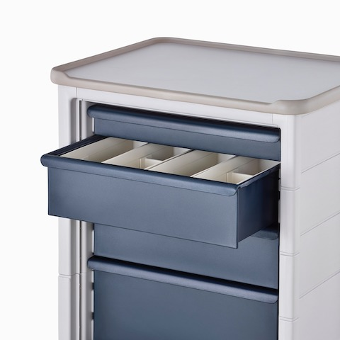 Detail of Procedure and Supply Cart in a soft white body and dark blue drawers with the top drawer open showing organizational subcontainers.