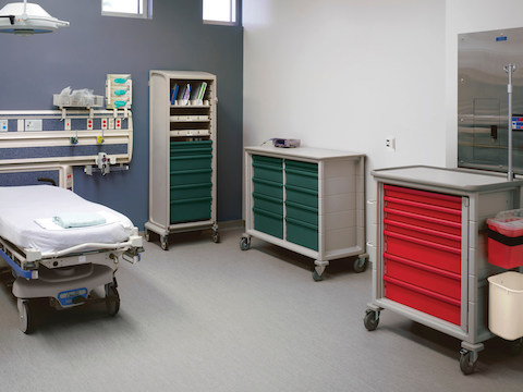 A procedure room containing three mobile Procedure/Supply Carts, one with an attached sharps container.