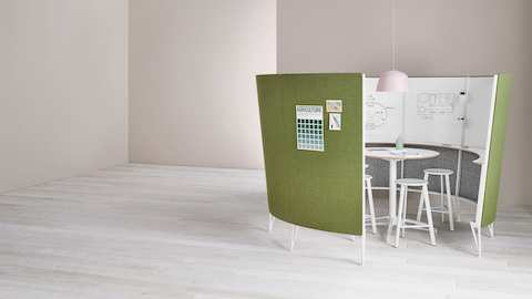 A set of Prospect Stools around a table in a Prospect Creative Space with green acoustic fabric and sketches on the whiteboards inside.
