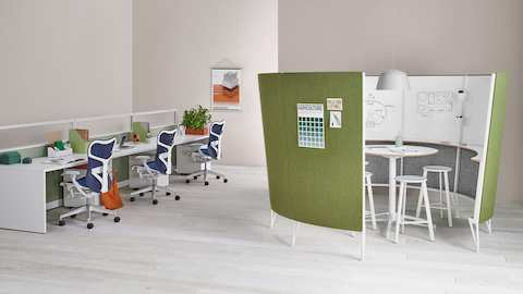A series of workstations with blue Mirra 2 ergonomic desk chairs near a Prospect collaborative space with green acoustic fabric on the outside.