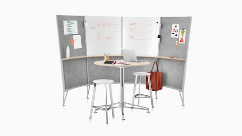 A 4-panel Prospect Creative Space with sketches and inspirational materials on the walls and stools around a table.