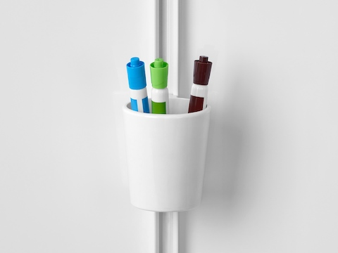 Green, blue, and brown markers sit in a white marker cup attached to the internal rail of a Prospect Creative Space next to a whiteboard.