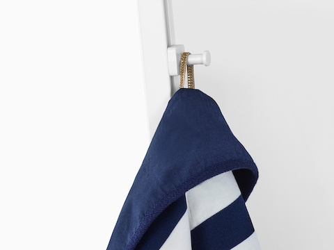 A  blue and white coat hangs from a white coat hook attached to the internal rail of a Prospect Creative Space.