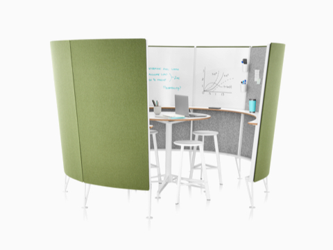 Stools around a table in a Prospect Creative Space with sketches on the interior whiteboards and green acoustic fabric on the outside.