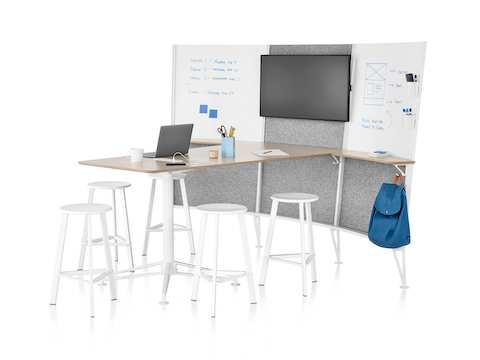 Five white stools surround the desk of a Prospect Media Space, with a laptop and a coffee cup on the desk and sketches on the whiteboards.
