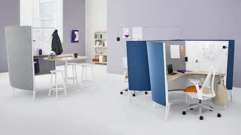 Two blue Prospect Solo Spaces with white Sayl Chairs near a Prospect Creative Space in an office with high ceilings and purple walls.
