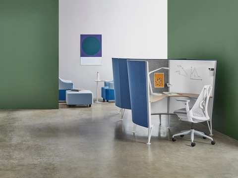 Two white Sayl Chairs in blue Prospect Solo Spaces near a lounge area with art on the walls and blue couches and lounge chairs.