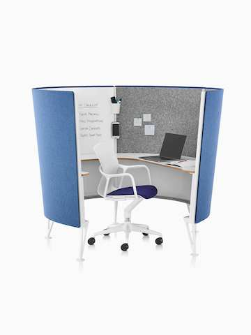 A Keyn office chair with white frame and dark blue seat pad in a blue 4-panel Prospect Solo Space with a laptop on the wraparound desk.