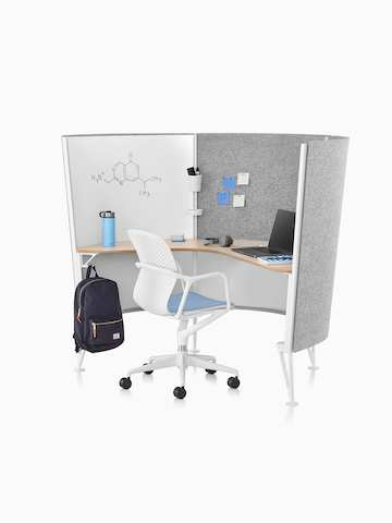 A white Keyn desk chair with light blue seat pad in a 3-panel Prospect Solo Space with sketches on a whiteboard and notes tacked to the walls.