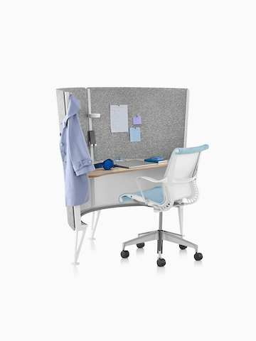 A Setu desk chair with white frame and light blue upholstery at a 2-panel Prospect Solo Space with notes tacked to the gray acoustic fabric.