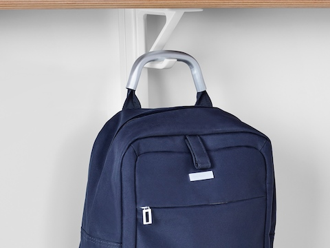A blue backpack hangs from a white bag hook underneath the desk in a Prospect Solo Space.