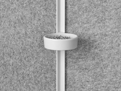 A white tack cup filled with gray thumbtacks attached to the internal rail of a Prospect Solo Space with gray acoustic fabric.