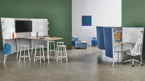 A group of white Prospect stools gathered around the table of a Prospect Media Space near two Prospect Solo workspaces with blue acoustic fabric.