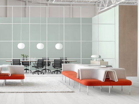 A Public Office Landscape setting featuring configurations of orange and white social chairs to support casual interaction.