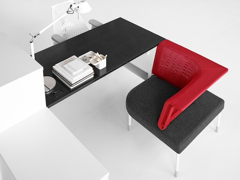 Overhead view of a Public Office Landscape workstation composed of a black surface, white storage, and red social chair.