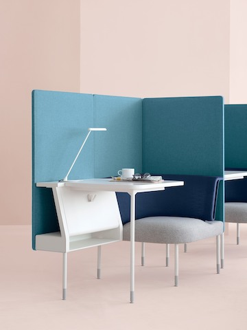 A small Public Office Landscape workstation, partially enclosed with blue privacy panels.